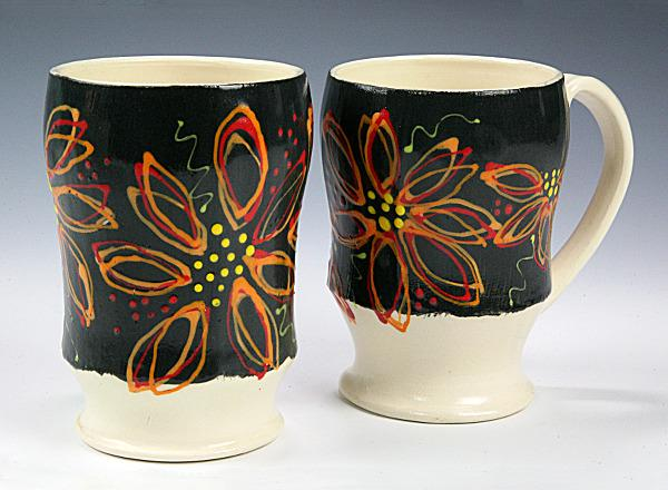 A pair of hand thrown ceramic mugs with multicolored decoration on white clay.
