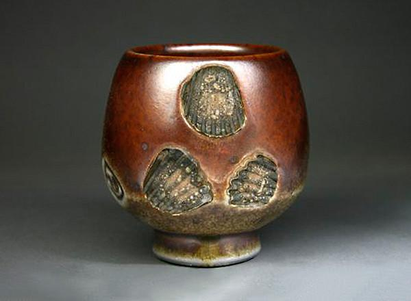 Rustic colored, hand thrown ceramic tea bowl with sea shell imprints.