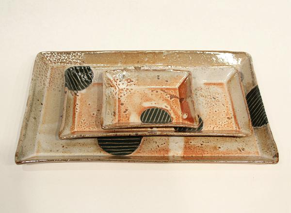 Stacking set of handmade serving trays with coffee colored glaze and embedded designs.