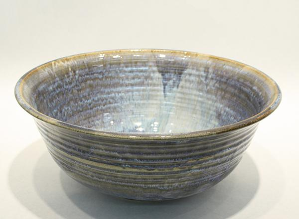 Large, hand thrown, tan and blue glazed ceramic serving bowl.
