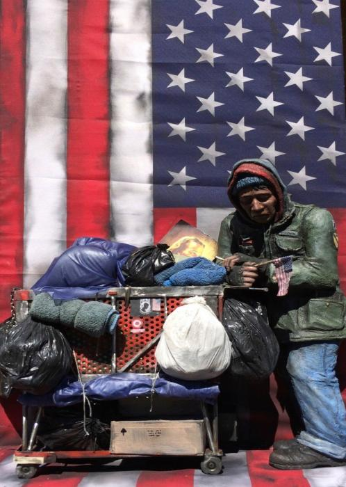 A clay homeless person with an overflowing shopping cart, holding and standing before American flags.
