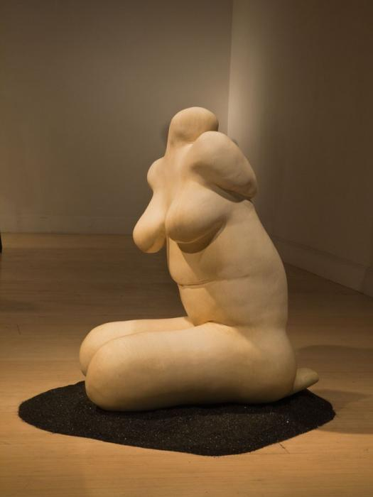 A headless, featureless female nude sculpted from clay.