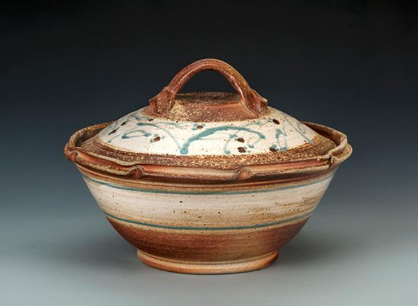 Wheel thrown, lidded casserole that is rustic colored with white bands and green highlights.