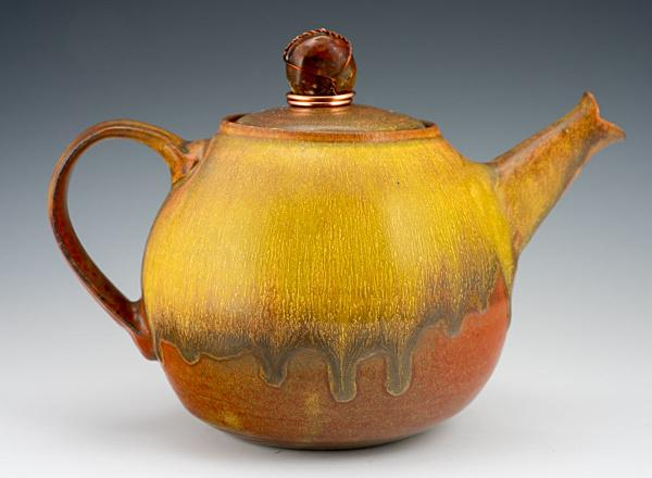 A hand thrown ceramic teapot with a rustic orange glaze.