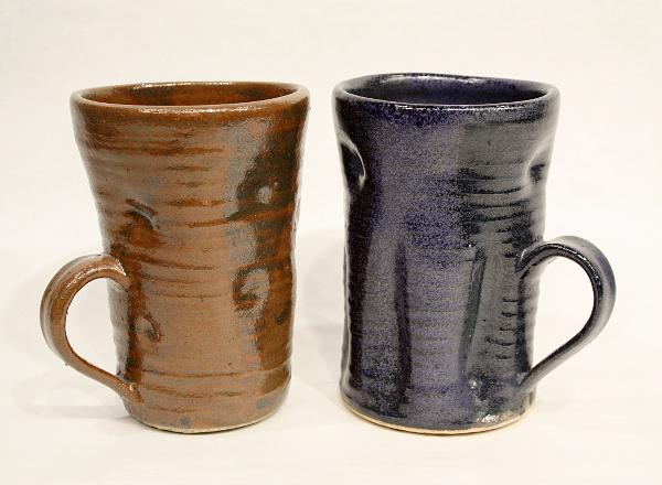 Pair of hand thrown drinking mugs: one with brown glaze and one with blue glaze.