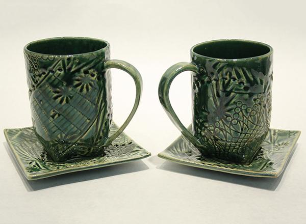 A pair of hand made, green glazed, ceramic cups and saucers.