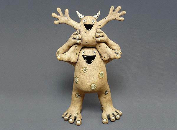 Two hand made ceramics creatures acting silly, one on the shoulders of the other.