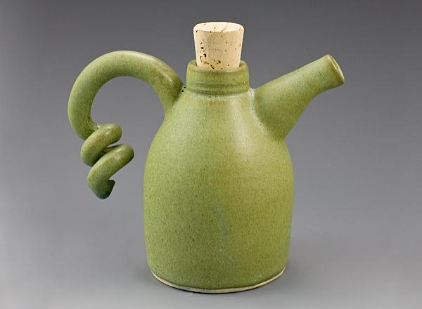 A hand thrown ceramic ewer with green glaze and corked lid.